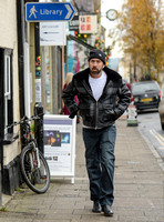 A bearded Nicolas Cage wearing plaid jacket and beanie hat, passing under blue library sign in Glastonbury, Somerset,