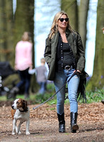 Supermodel Kate Moss wearing military style jacket, skinny jeans and cowboy boots takes a walk with her dog Archie in the woods
