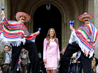Elizabeth Hurley in pink coat flanked by  two mexicans on stilts wearing ponchos, sombreros and shaking their maracas