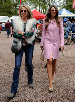 Georgia Daventry wearing jeans, brightly coloured blouse and fluffy gilet with Elizabeth Hurley in a pink coat both wearing sunglasses walking towards camera.