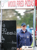 "Zara Phillips in blue MUSTO jacket at Pizza stand with ""Wood Fired Pizzas"" overhead."