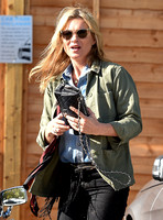 Kate Moss wearing military style jacket, teamed with denim shirt, black skinny jeans, tall Christian Laboutin leather boots carrying a vintage Chanel quilted flap bag.