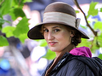 Laura Carmichael as Lady Edith wearing broad brimmed cloche style hat, head shot
