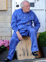 Sir Michael Gambon as Howard Mollison wearing blue pyjamas and monogrammed slippers sat on a tea cheast