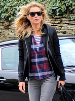 Half lengh. Kate Moss wearing trademark grey skinny jeans, Ray-Ban Wayfarer sunglasses, blue and white striped 'T', plaid shirt, hoodie with tailored jacket stood by her black Porche 911