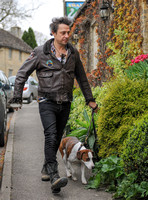 "Jamie Hince wearing black skinny jeans, scruffy boots and brown bomber style leather jacket, with dog  ""Archie"" on lead."