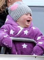 Laughing Mia Tindall in pink and white onepiece with woolly hat.