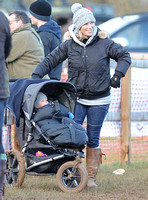 Zara Phillips wearing woolly hat, with daughter in blue buggy.