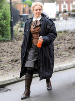 Amanda Abbington carrying orange drink, weraing period costume with long black coat over