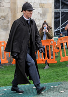 Benedict Cumberbatch wearing long caped coat and deerstalker walking from left to right.