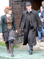 Amanda Abbington and Benedict Cumberbatch in costume smiling walking towards camera.