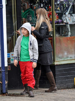 Kal-El Coppola Cage leaving jewellery shop with middle aged woman in Glastonbury, he is wearing Ralph Lauren hoodie, green T shirt, red trousers and heavy work style boots