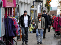 A bearded Nicolas Cage wearing plaid jacket and beanie hat, walking and talking to leather artisan in flat cap in  Glastonbury High Street, amongst others.