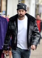 Close up of a bearded Nicolas Cage wearing plaid jacket and beanie hat, walking alone in Glastonbury, Somerset.