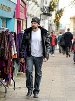 A bearded Nicolas Cage wearing plaid jacket and beanie hat, walking alone in busy Glastonbury High Street.