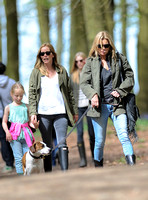 Supermodel Kate Moss wearing military style jacket, skinny jeans and cowboy boots takes a walk with her dog Archie and some pals  in the woods