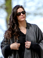 Actress Liv Tyler looking glamourous wearing large sunglasses and poncho - close-up.