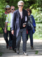 Full length shot of Peter Capaldi as Doctor Who wearing a long dark jacket, checked trousers and Ray Ban sunglasses, with others.