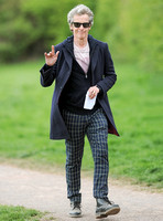 Full length shot of Peter Capaldi as Doctor Who wearing a long dark jacket, checked trousers and Ray Ban sunglasses waving to camera