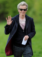 Close up of Peter Capaldi as Doctor Who wearing a long dark jacket, checked trousers and Ray Ban sunglasses waving to camera