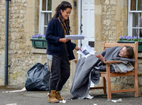 "Karla Crome with dreadlocks wearing blue jacket, grey trousers and workboots handing missing person notice to rough sleeper on park bench in a scene from ""Apocalypse Slough"""