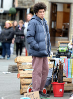 "Joel Fry wearing blue padded jacket and pinkish trousers in a market scene during filming ""Apocalypse Slough"""