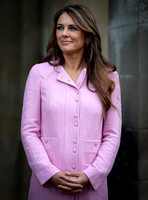 Elizabeth Hurley, pink coat, waist up, hands linked in front.