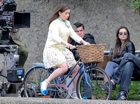 Emilia Clarke on bicycle with handlebar basket wearing lemon floral dress, lemon jumper and turquoise neckerchief