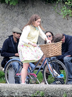 Emilia Clarke looking shakey on bicycle with handlebar basket wearing lemon floral dress, lemon jumper and turquoise neckerchief