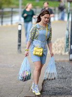 Emilia Clarke on set carrying two plastic varrier bags of shopping, wearing pale blue dungaree dress with heart motif, pineapple print jumper, blue ankle socks with lemonT bar shoes and a yellow mini