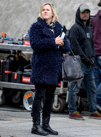 Jojo Moyes wearing navy coat, black tight and black boots on film set