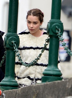 Emilia Clarke on set wearing white fur jacket with black stripes by green railings