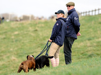side shot ofZara Phillips in blue MUSTO jacket and polo cap on hillside  with boxer and labrador with unknown older male