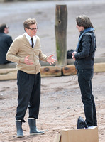 Colin Firth on Teignmouth beach, hands gesticulating, wearing beige cardigan talking to director James Marsh
