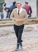 Colin Firth on Teignmouth beach, hands clenched loosely in front wearing beige cardigan, white shirt with brown tie, dark grey trousers and sailing boots
