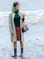 Rachel Weisz on beach carrying handbag, wearing 60's style pale green raincoat, headscarf and blue short wellington boots