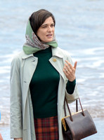 Close up of Rachel Weisz on beach carrying handbag, wearing 60's style pale green raincoat and headscarf
