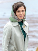 close up  of Rachel Weisz wearing 60's style pale green raincoat, headscarf