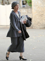 Penelope Wilton (Isobel Crawley) wearing grey suit and matching hat wearing Mary Jane button shoes and carrying a coat over arm.