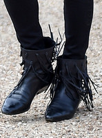 close up view of black leather fringed ankle boot