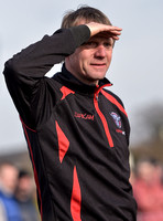 Stuart 'Psycho' Pearce for Longford AFC wearing team tracksuit watching game with eyes shielded from the sun, waist up.