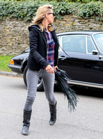 wearing trademark grey skinny jeans, black boots and a pair of Ray-Ban Wayfarer sunglasses, striped 'T', plaid shirt, hoodie with tailored jacket,  carrying Genevieve Jones fringed bag