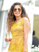 Attractive female wearing RayBan aviator sunglasses and a yellow lace dress holding a champagne flute