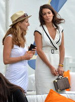 Stephanie Mendoros wearing white dress with black detail and carrying an Aspinal mini trunk clutch bag