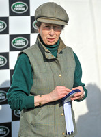 Princess Anne holding rosette wearing matching tweed hat and body warmer