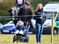 Mia Tindall, groom and family friend watch from outside the arena