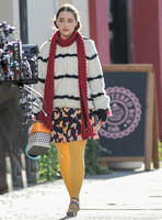 Emilia Clarke on set wearing white with black stripe fur jacket, long red scarf, flowered skirt and yellow tights.