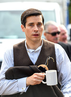 Rob James-Collier waring shirt and waistcoat looking directly at camera carrying jacket on clothes hanger and a white ceramic mug