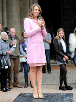 Elizabeth Hurley wearing pink stood on rostrum with microphone