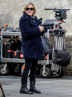 Jojo Moyes in sunglasses wearing navy coat, black tight and black boots on film set